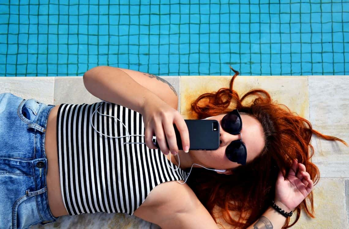 woman at the pool using a sim card